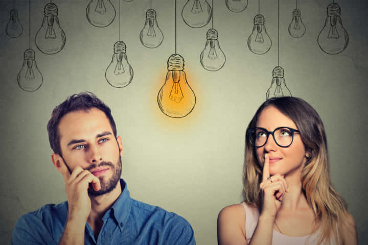 Cognitive skills ability concept, male vs female. Young man and woman looking at bright light bulb isolated on gray wall background