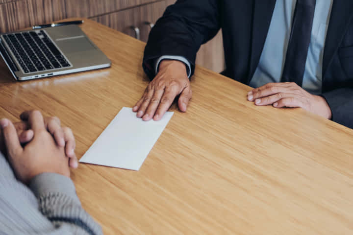 Hand of employer filing final remuneration to employee, letter of resignation, resign concept.