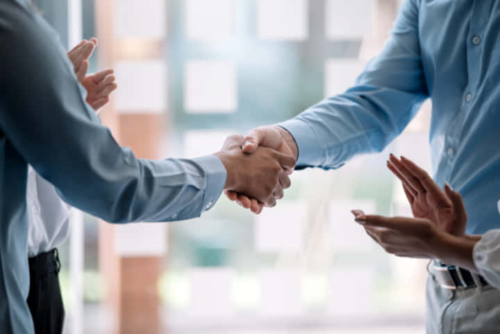 Teamwork of business people at meeting shaking hands to seal a deal with his partner.