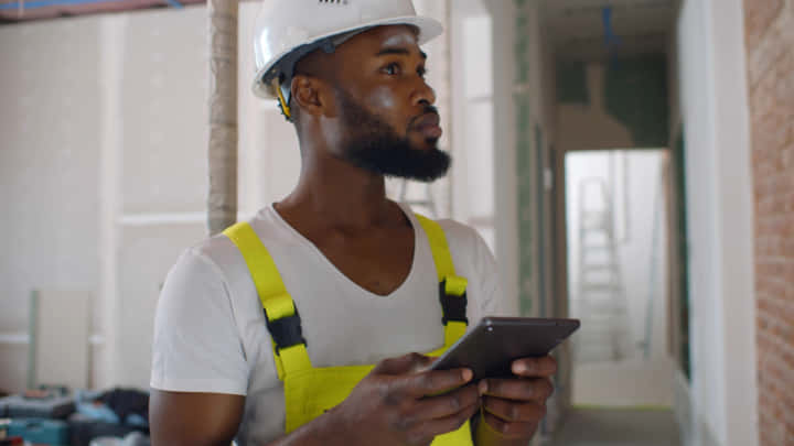 African architect inside house being renovated using digital tablet. Portrait of afro-american builder in uniform and helmet checking blueprint on tablet computer